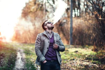 Man with beard vaping outdoor e cigarette